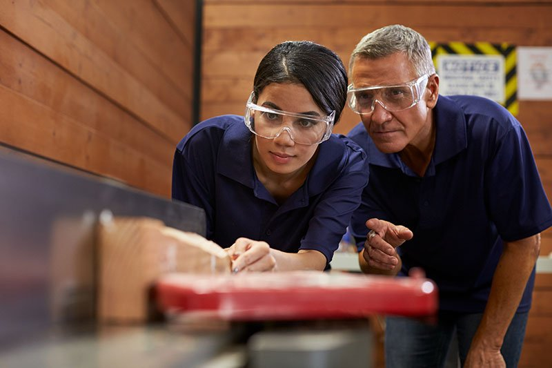 older man showing young female how to use a table saw